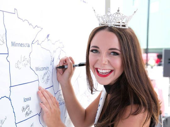 Miss Wisconsin signs the Miss America map.