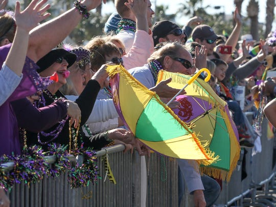 Parade-goers use parasols to catch throws during the