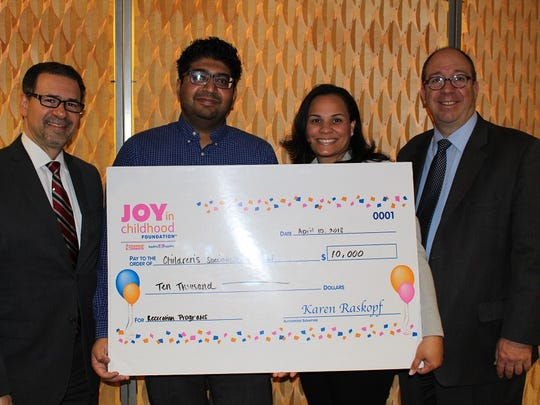 The Joy in Childhood Foundation presents a $10,000 check to Children's Specialized Hospital Foundation. From left: Charles Chianese, vice president, chief operating officer of Children's Specialized Hospital; Miten Patel, Dunkin' Donuts franchisee; Stacey Goetz, operations manager, Dunkin' Brands; and Philip Salerno lll, president and chief development officer, Children's Specialized Hospital Foundation.