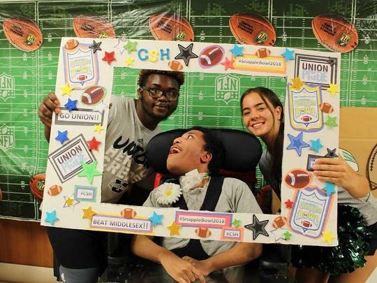 "Damien, a patient in the Long Term Care Unit at Children's Specialized Hospital, is all smiles as he takes a few pics in the ""selfie booth"" with members of the Snapple Bowl XXV all-star football and cheer teams."