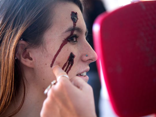 Megan McDaniel gets her makeup done by Karley Ree Ward at the Old Town Zombie Fest in Fort Collins Saturday, Oct. 25, 2014.