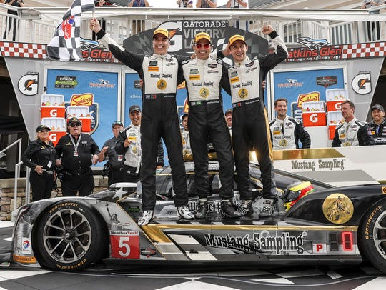 Action Express Racing teammates Joao Barbosa, left, Christian Fittipaldi, center, and Al Albuquerque celebrate in Victory Circle after their win in the 2017 Sahlen's Six Hours of The Glen at Watkins Glen International.