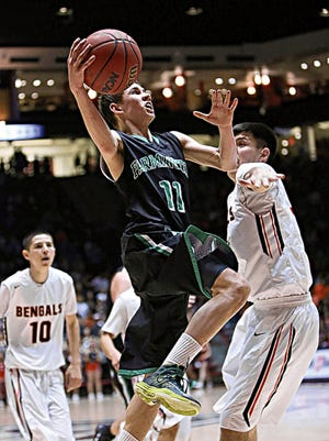 Farmington's Berrett Bentley drives around Gallup's Colton Lowley for a layup in their 5A state quarterfinal game at The Pit in Albuquerque on March 11.
