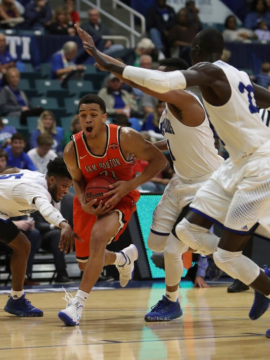 Sam Houston State guard Paul Baxter (21) is swamed by New Orleans defenders during the second half of an NCAA college basketball game in the Southland Conference tournament Friday, March 10, 2017, in Katy, Texas. (Steve Gonzales/Houston Chronicle via AP)