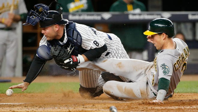 New York Yankees catcher Brian McCann loses the ball as Oakland Athletics' Chris Coghlan scores on a Josh Reddick single during the fourth inning of a baseball game in New York, Wednesday, April 20, 2016.