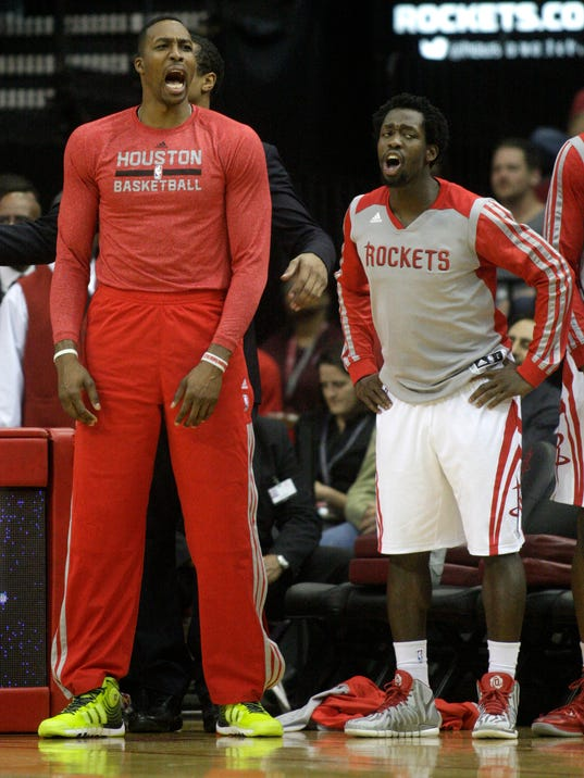 Houston Rockets' Dwight Howard, left, and Pat Beverley let out a yell during the fourth quarter of an NBA basketball game against the Minnesota Timberwolves, Thursday, March 20, 2014, in Houston. The Rockets defeated the Timberwolves 129-106. (AP Photo/Patric Schneider)
