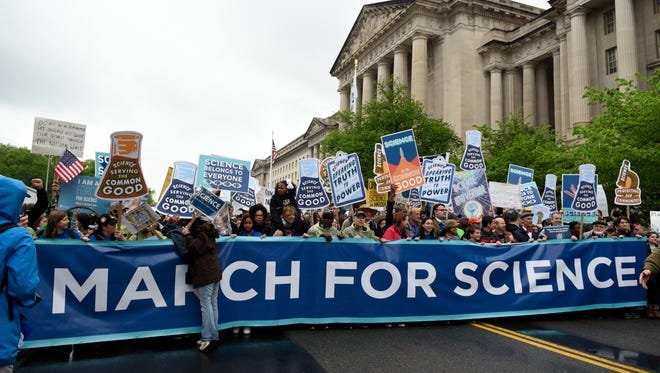 People carry a March for Science banner and signs as they pass the U.S. Environmental Protection Agency during the March For Science in Washington, Saturday, April 22, 2017.  Advocates marched in more than 500 cities, including St. Paul, where at least 10,000 voiced their support for science funding. Scientists, students and research advocates rallied from the Brandenburg Gate to the Washington Monument on Earth Day, conveying a global message of scientific freedom without political interference and spending necessary to make future breakthroughs possible.