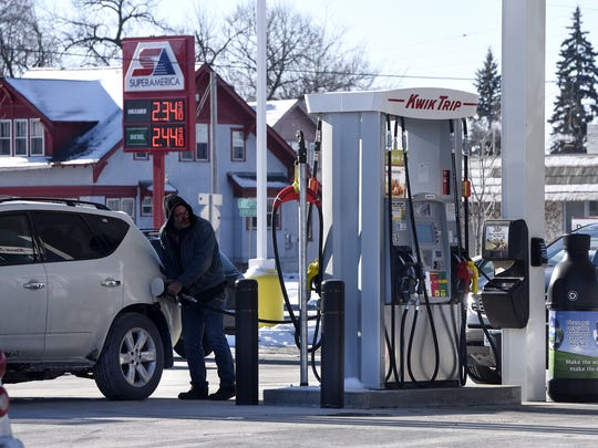 A customer fills his tank at the Kwik Trip on Division