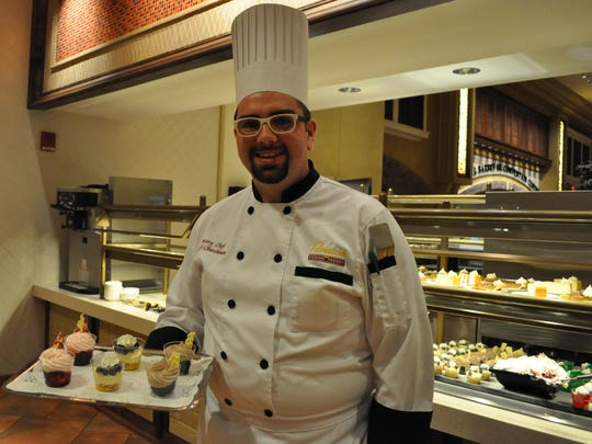 Jacob Churchman holds a tray of parfait cups, one of the new items he has added to Paragon Casino Resort's desert selection since being hired as head pastry chef.