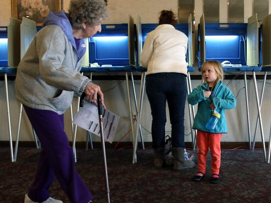 Raegan Zilles puts on her I voted sticker while her mom Andi casts her ballot for the presidential primary at the Elks Lodge in Waukesha Tuesday, April 5, 2016. Hotly contested races for both the Democrats and Republicans have energized voters.