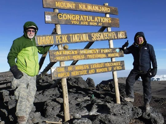 Dan Repasky and Marty Bannon stand on the top of Mount Kilimanjaro.