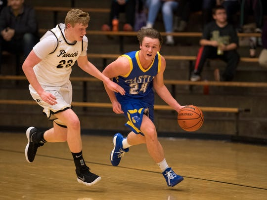 Castle's Jace Stieler (24) heads up the floor against Boonville's Hunter Bruce (23) at Boonville High School Tuesday night. The Knights beat the Pioneers 77-60.