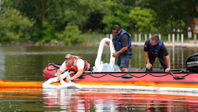 Members of Fond du Lac Fire/Rescue put down a boom system to contain and collect an oil spill in the Fond du Lac River north of Scott Street Monday June 19, 2017. The orange piece contains the oil while the white part absorbs it. Doug Raflik/USA TODAY NETWORK-Wisconsin