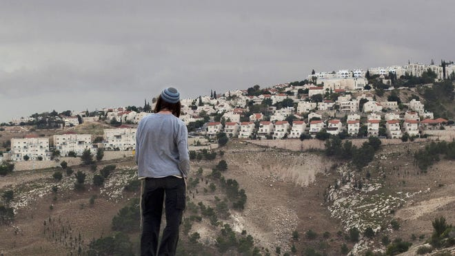 In this Dec. 5, 2012, photo A Jewish settler looks at the West bank settlement of Maaleh Adumim, from the E-1 area on the eastern outskirts of Jerusalem.