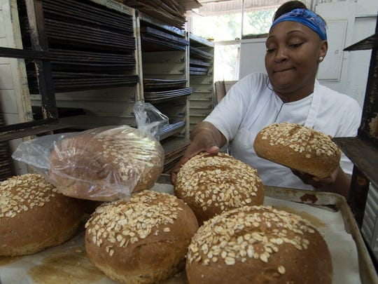 Isha Reyner, an employee of Artisan Bread, handles ciabatta bread at the newly opened bakery on Fowler Street in Fort Myers Tuesday.