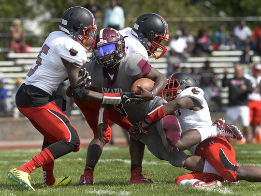 Greece Arcadia's Robert Smith, center, fights for extra