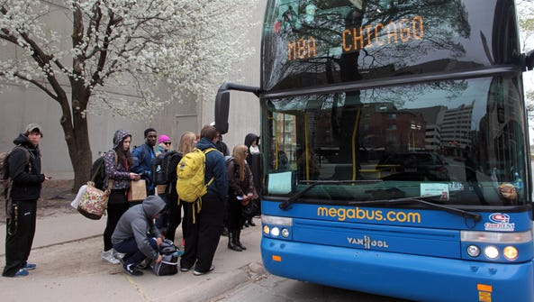 In this file photo from 2013, passengers get into a