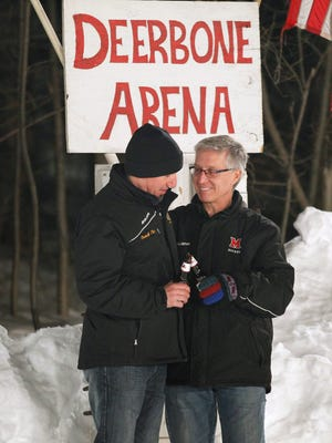 "Deer Bone Arena owner Brian Stancampiano, right, has a toast on the ice with arena ""Hall of Famer"" Tim Randall, left, in front of the arena sign in Perinton."