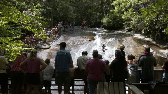 Sliding rock draws a crowd in the file photo. The popular attraction in Pisgah National Forest has reopened.