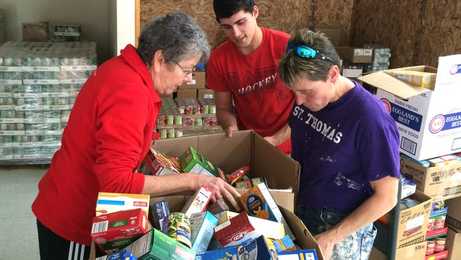 From left: Terri Rapp, Cody Kohls and Karlene Dillingham help organize food at the new South Wood County Emerging Pantry Shelf, 331 12th Avenue South, on Nov. 3, 2015.