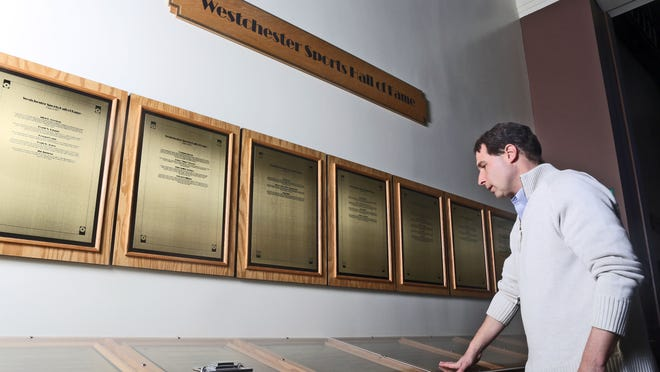 Mark Shevrin of Irvington looks at the names on the plaques in the Westchester Sports Hall of Fame at the Westchester County Center Dec. 17, 2014. He was unaware of the Westchester Sports Hall of Fame until he came across it while visiting the County Center to purchase tickets to see a New York Knicks D-League game. The Hall of Fame was recently refurbished and moved into one of the lobbies at the County Center.