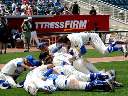 Players dog pile Josh Chavarria after he got a strikeout to clinch the 6A state title Saturday.