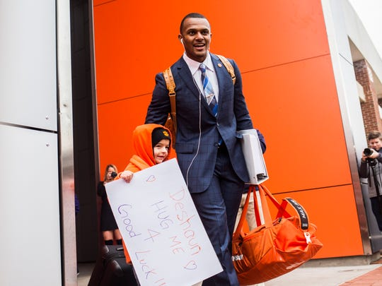 Clemson quarterback Deshaun Watson hugs a young fan while walking out between rows of fans to board a bus at Memorial Stadium before Clemson's departure for the national championship game.