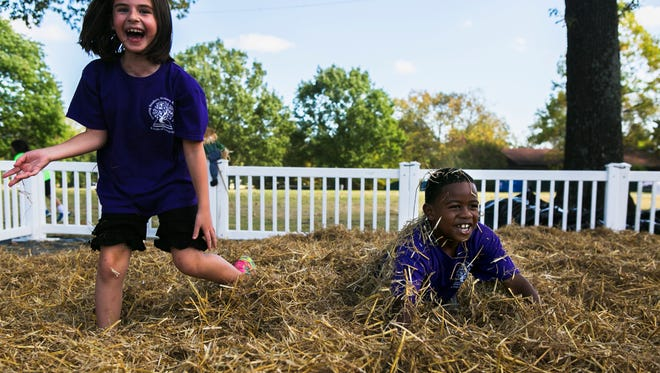 "October 18, 2016 - Riley Ware, 7, laughs as Jaylen Jeffries, 7, emerges to the surface after being buried in hay by fellow classmates during a field trip to the Memphis Botanic Garden on Tuesday. The students are in the second grade at Lewisburg Primary School in Olive Branch, Mississippi. ""We're ready for fall,"" Lisa Lloyd said, a second grade special education teacher. ""We picked a perfect day to come."""