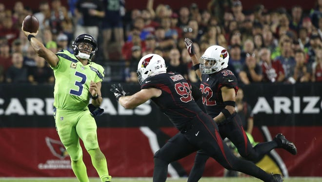 Seahawks Russell Wilson (3) throws a pass on the run from Cardinals Josh Mauro (97) and Tyrann Mathieu (32) during the fourth quarter on Nov. 9, 2017 at University of Phoenix Stadium in Glendale, Ariz.