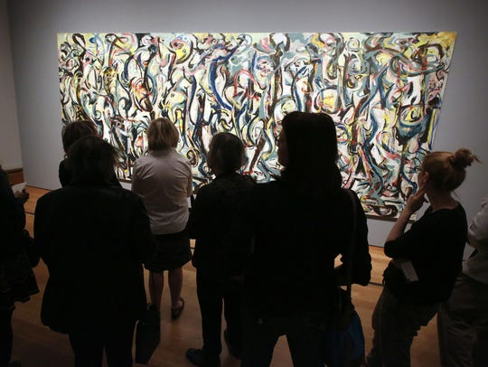"Members of the media view Jackson Pollock's ""Mural"" in 2014 at the J. Paul Getty Museum in Los Angeles. The painting, valued at $140 million, is owned by the University of Iowa."