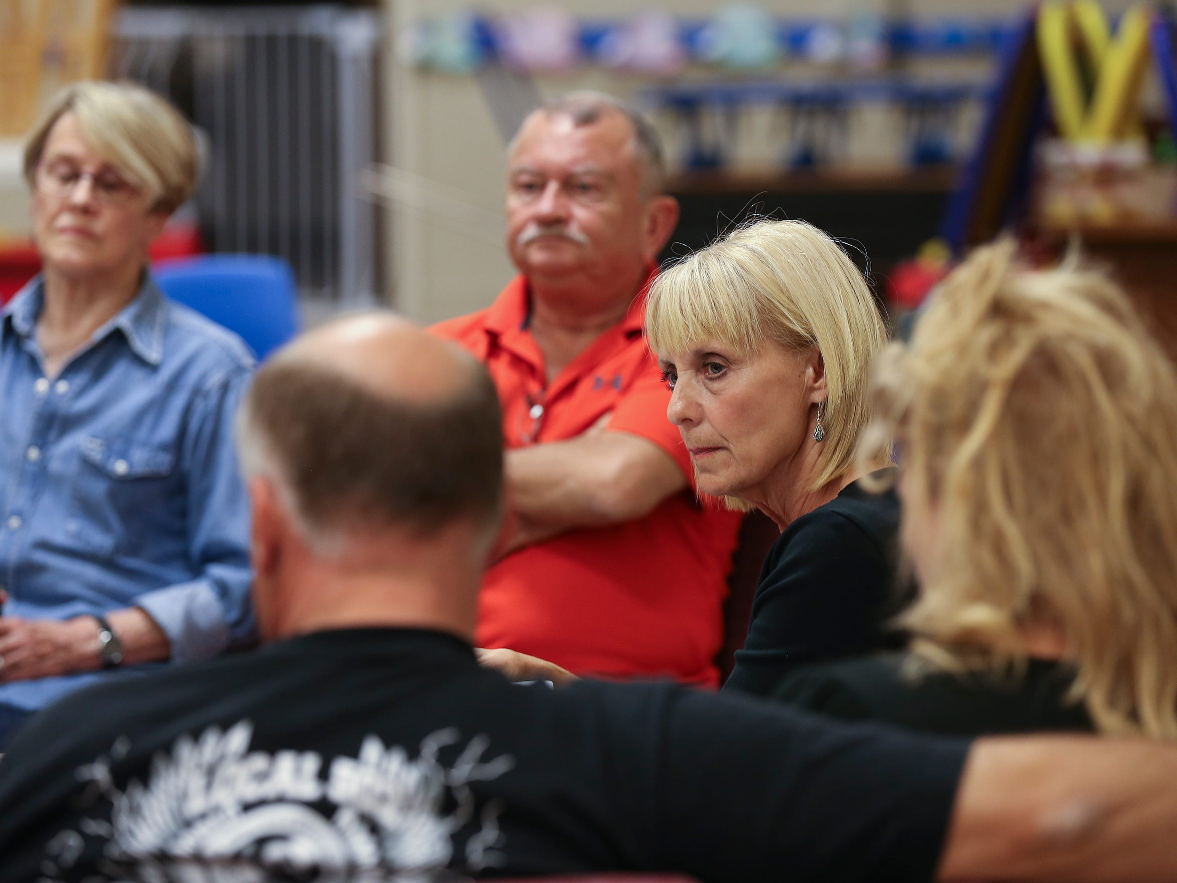 Brenda Cooley, center, listens to members as she conducts