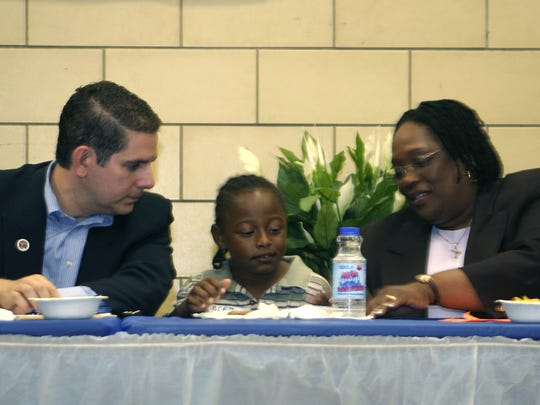 Genesee resident Erik McLinton, 8, a member of the neighborhood after-school program, flanked by Mayor Virg Bernero, and Joan Jackson Johnson, Lansing's Director of Human Relations and Community Services, Aug. 5, 2007.