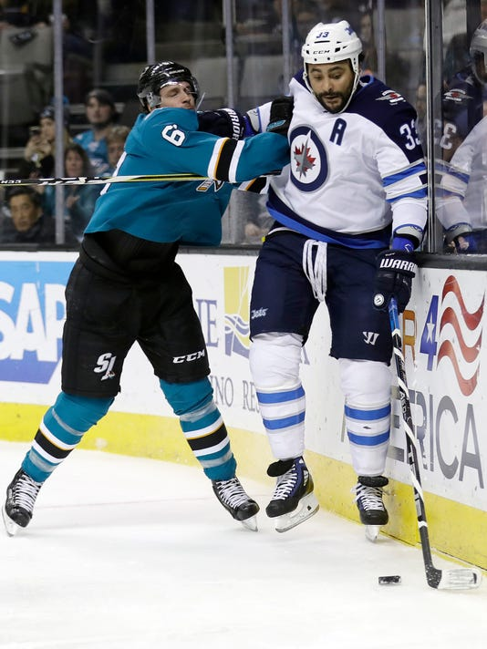 Winnipeg Jets defenseman Dustin Byfuglien (33) is pushed against the boards by San Jose Sharks defenseman Justin Braun during the first period of an NHL hockey game Tuesday, Jan. 23, 2018, in San Jose, Calif. (AP Photo/Marcio Jose Sanchez)