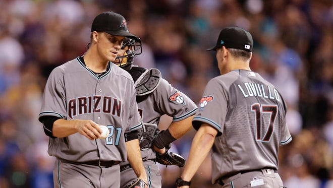 Jun 20, 2017: Arizona Diamondbacks starting pitcher Zack Greinke (21) hands the ball off to manager Torey Lovullo (17) in the eighth inning against the Colorado Rockies at Coors Field.