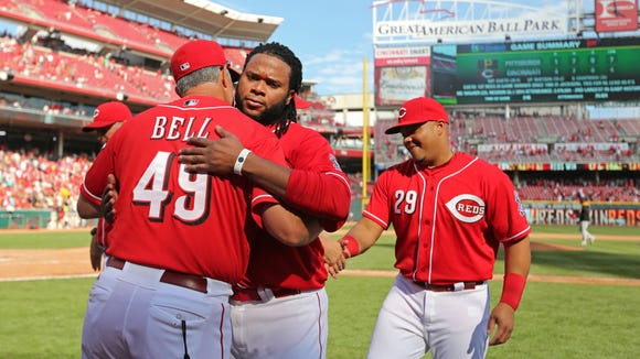Reds pitcher Johnny Cueto is congratulated by bench coach Jay Bell after winning his 20th game of the 2014 season on Sept. 28.