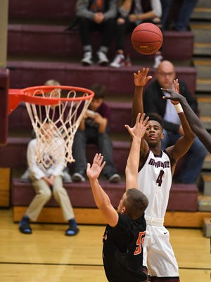 Dowling's Sam Ingoli (4) goes up for a jumper on Tuesday, Dec. 13, 2016, during a basketball game between the Ames Little Cyclones and the Dowling Maroons at Dowling Catholic High School.