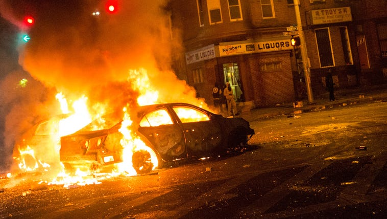 Two cars burn in the middle of an intersection at New