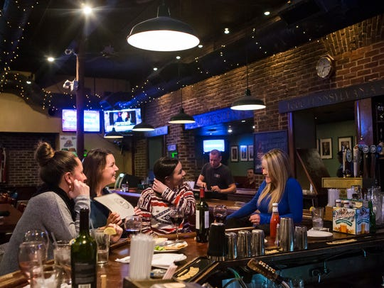 Patrons hang out at the bar at Dead Presidents on Wednesday
