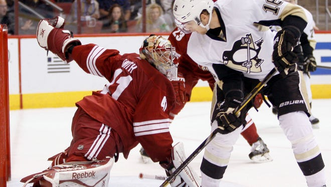 Coyotes goalie Mike Smith makes a right-pad save against Brandon Sutter of the Pittsburgh Penguins during a 3-1 Coyotes victory at then-Jobing.com Arena on Feb. 1, 2014.