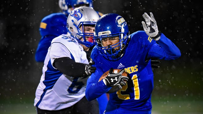 Cathedral's Kendrick Hernandez tries to escape a tackle by Tedd Otto of Foley during the first half of the Tuesday, Oct. 25, game at Husky Stadium in St. Cloud.