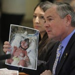 Senator Bill Sharer, R-Farmington, holds up a picture of his granddaughter Scarlet Sharer 2 hours after she was born at the Senate Public Affairs Committee on Tuesday, while discussing Senate Bill 242 and 243. Scarlet was born one month premature.