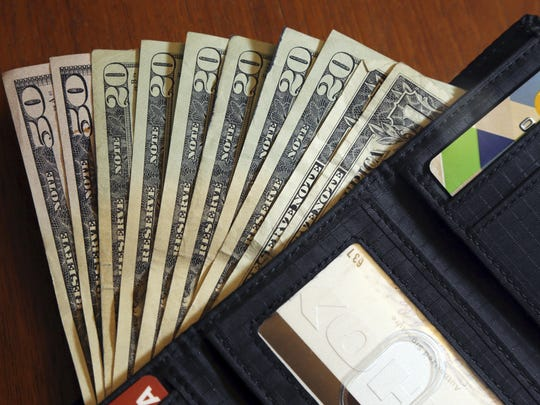 In this June 15, 2018 photo, cash is fanned out from a wallet in North Andover, Mass.