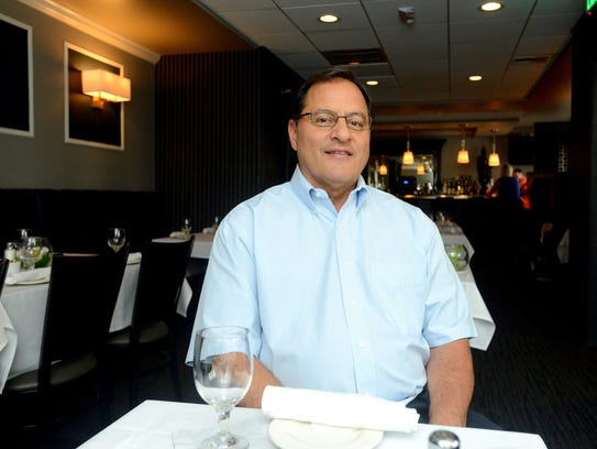 Knight Cap owner Leo A. Farhat Jr. sits in the remodeled