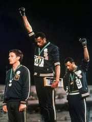 "Extending gloved hands skyward in racial protest, U.S. athletes Tommie Smith (center) and John Carlos stare downward during the playing of ""The Star-Spangled Banner"" after Smith received the gold and Carlos the bronze medal in the 200 meter run at the Summer Olympic Games in Mexico City on Oct. 16, 1968."