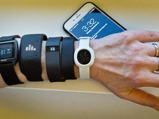 Fitness trackers, from left, Basis Peak, Adidas Fit Smart, Fitbit Charge, Sony SmartBand, and Jawbone Move, are posed for a photo next to an iPhone, in New York.