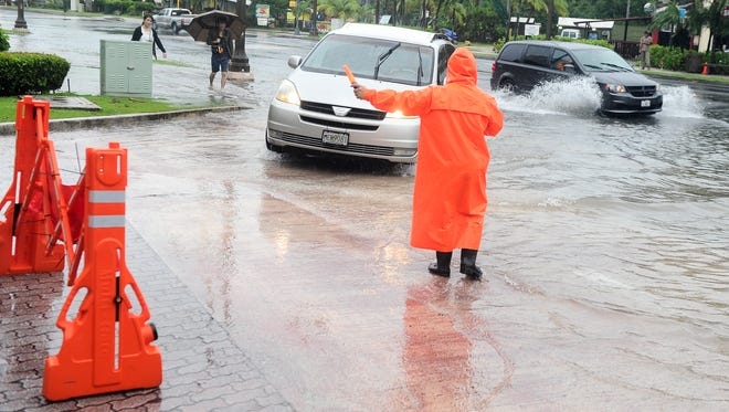 Security personnel Shaun Cruz uses light wands to warn drivers of deep ponding water at the driveway entrance of the Hyatt Regency Guam in Tumon on Thursday, Aug. 4.