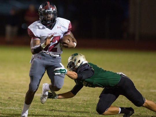 Desert Ridge senior running back Taren Morrison breaks the tackle of Skyline senior safety Zach Olague on Friday, Oct. 10, 2014, in Mesa.