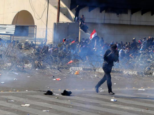 Protesters run from tear gas fired by security forces during protests for followers of Iraq's influential Shiite cleric Muqtada al-Sadr in Tahrir square, Baghdad, Iraq, Saturday, Feb. 11, 2017.