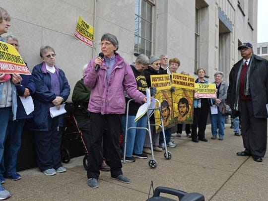 """Benedictine Sister Anne McCarthy leads a """"Build Bridges Not Walls'' immigration vigil at Perry Square near the U.S. District Courthouse in Erie, Pa., Wednesday, Feb. 22, 2017. About 60 attended the vigil, where speakers denounced President Donald Trump's temporary immigration and refugee bans."""