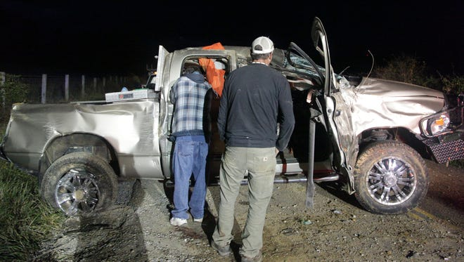 Friends of a driver whose truck overturned on Middlebrook Rd. collect his valuables for safekeeping before the wreck is towed away on Saturday evening, Oct. 18, 2014. The driver was air-lifted to UVa.
